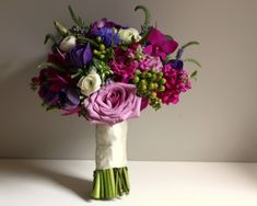 Blue Cornflowers, Fuchsia Stock, Purple Roses, Veronica, Lisianthus, Hypericum Berries, Ranunculus,  Anemones and other seasonal blooms completed this bouquet