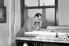 Oscar Niemeyer, one of the original architects of United Nations Headquarters in New York, going over plans for the building on 18 April 1947. UN Photo