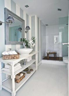 Un baño muy chic con papel a rayas en la pared y apliques de pantalla.