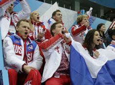 The Russian team cheer for Evgeny Plyushchenko of Russia as he competes in the men's team short program figure skating competition at the Ic...