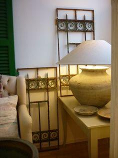 Interieur in grijsgroen; grote lampvoet en -kap, oude hekjes, marmeren schaaltjes.