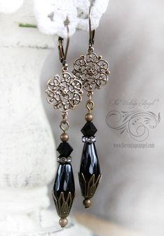 Victorian inspired and dramatic, these dark beauties feature real onyx drops paired with darkened brass bead caps. Aged brass filigree flowers suspend the drop assembly crafted from onyx faceted teardrops and Swarovski jet black bicones. A rhinestone rondelle adds just a pop of elegance. Hung from leverback hooks in aged brass for pierced ears.    All components are American-made brass, free of lead and nickel   About 2.95