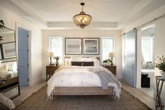 elegant farmhouse style master bedroom with a dark woven rug, double windows, a sliding barn door, and accent nightstand tables. Modern Farmhouse Exterior, Modern Farmhouse Style, Farmhouse Interior, Farmhouse Plans, Modern Master Bedroom, Master Bedrooms, Dining Chair Slipcovers, Bedroom Paint Colors, Visual Comfort