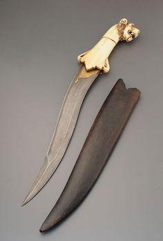 ANCIENNE DAGUE MOGHOLE  INDE, XIXE SIÈCLE  Le manche en os sculpté d'une tête de tigre, la lame ornée d'un décor  damasquiné de volutes; étui en cuir.    L: 40cm - 15.75''
