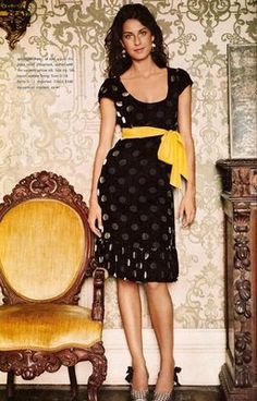 Love the pop of yellow from the sash on this black velvet polka dotted dress.