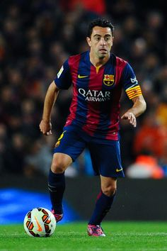 Xavi Hernandez of FC Barcelona a runs with the ball during the La Liga match Between FC Barcelona and Real Madrid CF at Camp Nou on March 22, 2015 in Barcelona, Catalonia.