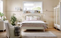 A bedroom in country style with a large bed, two bedside tables, chest of 3 drawers and two wardrobes, all in white.