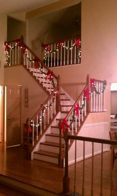 Garland, lights and bows on the front staircase for Christmas