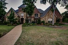 2002 Sovereign Oak Ct, Arlington, TX | $990,000 | 5 Bed | 5.1 Bath | 5,600 sqft. Richly appointed throughout, designer fixtures, beamed ceilings, professional kitchen with gas range, griddle, pot filler, dual dishwashers, butlers pantry, moms office, wine cellar, media room, game room, master suite with sitting area, guest suite with private entry and courtyard. Lush landscaping, outdoor living area with fireplace.
