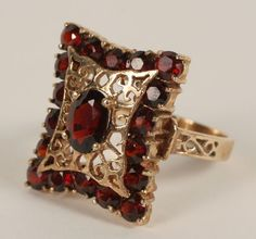 Gold marked 14K Victorian style garnet ring with openwork detailing. 19x15mm setting. Size 6 3/4. 4.8 grams.