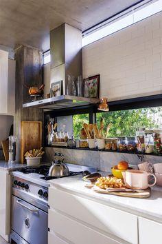 Cocina abierta con ventana al jardín, con utensilios y frascos en exhibición.