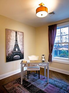 Royal purple curtains, an eclectic area rug and an Eiffel Tower print create a charming European feel in this contemporary home office.