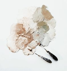 smudges of browns, flesh tones, and whites below two palette knives