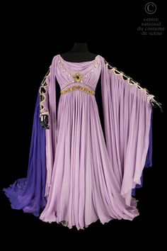 Opera National de Paris Long chiffon dress lined with purple gray crepe satin. V neckline edged with a gold chain, beads and jewelry. Long Sleeve flesh with purple and violet tulle veil fastened by a gold braid way fibula. Gold belt packed with stones.