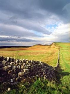 Hadrian's Wall Northumberland England  constructed by the Romans in 118 AD to prevent barbarian invasion of Brittania.   Wall is 70 miles long, 15-20 feet tall, 10-20 feet thick.  Still exists and may be walked today.