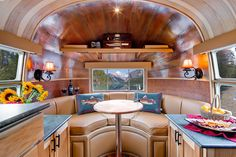 ROOM FOR ENTERTAINING AND MORE in this Airstream living room.  The forward end of the trailer, with its semi-circular natural leather sofa and ample counter space, is suitable for comfortable dining and small party hosting, as well as quiet time.