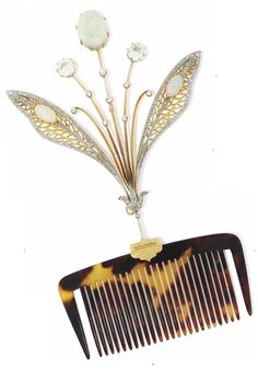 AN ART NOUVEAU OPAL AND DIAMOND HAIR COMB, CIRCA 1900. Composed of an old-cut diamond spray with central oval opal cabochon surmount, flanked to either side by pierced rose-cut diamond wing design panels, each with further opal cabochon accents, mounted en tremblant in silver and gold, 14.8cm. #ArtNouveau #comb