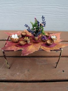 Fairy table - twig frame topped with glycerin-preserved leaf? The tiny containers (acorn caps, etc) are adorable, and I especially like the miniature flower arrangement -
