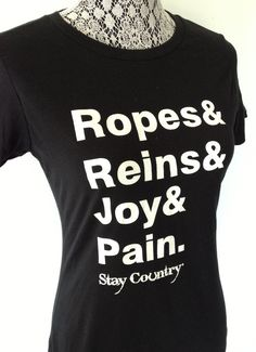 """It's the ropes and the reins and the joy and the pain and they call the thing RODEO.""  Whether you participate or spectate, this is the perfect shirt to wear to this years rodeo events... or just hanging out on any given day.  Women's black t-shirt with white screen print"