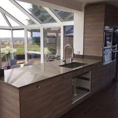 This brown style kitchen is added with a wood effect on the cabinets and our stunning Mocha style quartz. The stainless steel appliances and features are bought out in this kitchen against the brown hues and really make a modern twist to the perfect room in the home. #MochaQuartz #BrownQuartz #QuartzWorktops #BrownWorktops