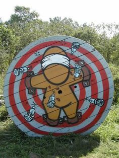 I love the target idea... Probably with just a boring, traditional, red and white target design. ;)  Archery target? From a huge electrical cable spool