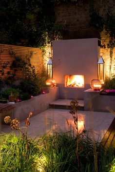 Urban Fireside Garden | Fireplace lit up at night in contemporary town garden | Charlotte Rowe Garden Design