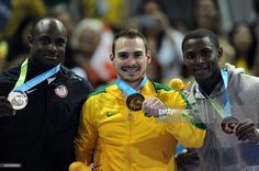 July 14 - Gymnastics Artistic - Men's - Rings. Gymnastics rings gold meal winner Brazilian Arthur Zanetti (C), silver medalist USA's Donnell Whittenburg (L), and bronze medalist Cuba's Manrique Larduet pose for a picture on the podium at the 2015 Pan American Games in Toronto, Canada, on July 14, 2015. AFP PHOTO/HECTOR RETAMAL