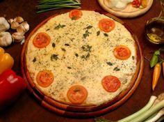 Receita de Falsa pizza - 1 1/4 de xícara (chá) de farinha de trigo (200 g) , 40 g de creme de queijo em pó (3 colheres de sopa) , 1 colher (sobremesa) de fermento em pó (10 g) , 150 g de creme de leite com soro (1 xícara de chá + 2 colheres de sopa) , 1 cabeça pequena de alho assado (30 minutos a 180° C) , 500 g de queijo muçarela ralado grosso , 500 g de tomate em rodelas médias temperadas com sal e escorridas na peneira , Orégano e sal a gosto , 50 g de queijo parmesão ralado no ralo fino…