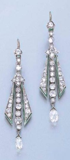 A PAIR OF ART DECO DIAMOND EAR PENDANTS, CIRCA 1930. Each briolette-cut diamond bordered by diamond and green enamel triangular-shaped pendants, suspended by a central collet line, from a trefoil and collet surmount with emerald detail, 6.0 cm. long. #ArtDeco #earrings