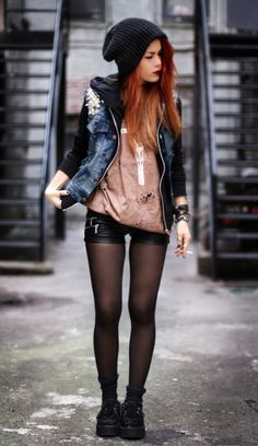 Black hoodie under a denim vest, with leather shorts and sheer tights.