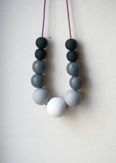 Handmade statement necklace featuring 11 hand painted wooden beads in Brilliant White (largest center bead), Smoke (large size beads), Dark Gray