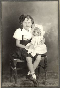 Girl on a stool with her doll.