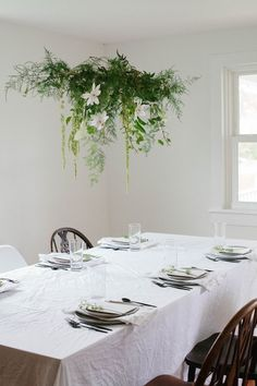 Hanging greenery centerpiece over spring table Hanging Centerpiece, Greenery Centerpiece, Hanging Table, Diy Hanging, Table Centerpieces, Flower Installation, Floral Chandelier, Green Table, Hanging Flowers