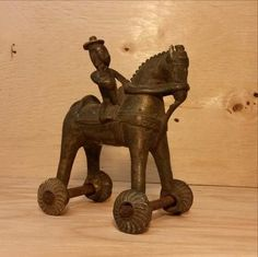 VINTAGE BRASS INDIAN TOY HORSE ON WHEELS.