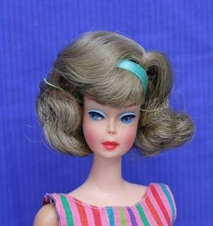 A beautiful high color American Girl with ash blonde hair in a side part.