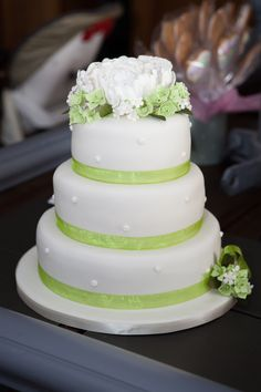 White three tiered wedding cake with lime green ribbon and flowers for detailing.