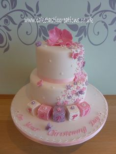 A pretty pink, white and lilac christening cake with the flowers cascading down the side