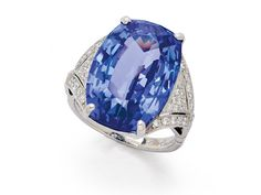 A Tanzanite and Diamond Ring   Set with a cushion-shaped tanzanite weighing approximately 19.50 carats, between tapering geometric diamond-set shoulders and scroll gallery, mounted in platinum, with Hallmarks for London, circa 1998
