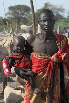 Africa | Atwot Dinka man carrying a small child, in the cattle camp in Buhayrat. Sudan | © Ngari Norway