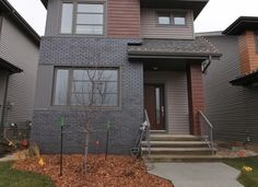 This residential development utilizes our SAGIWALL, in a number of different wood grain finishes, for accent features on the exterior of each home. Take out the last pictures of the sagiper soffit mocha redwood in this folder. #design #exterior