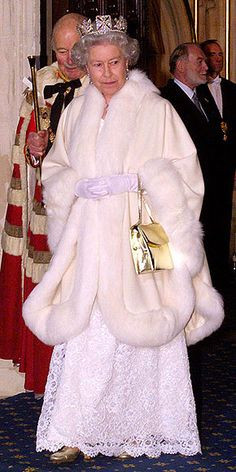 THE WHITE QUEEN    Opting for another favorite color – white – the Queen opened Parliament in 1998 in a dazzling long lace gown, a dramatic fur-trimmed coat and perfectly-matched golden accessories. She accented her look (naturally) with a beautiful crown.