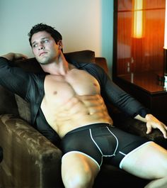 Buffed hunk with chiseled abs wearing a black trunk brief and black long sleeve shirt