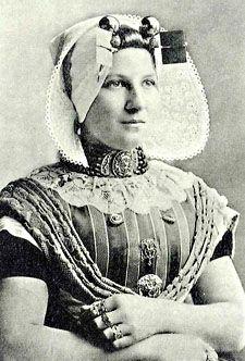 Protestantse vrouw uit Zuid-Beveland, circa 1890. Ze draagt diverse sieraden, zoals een groot filigrain voorslot, borstzeugen met bijbehorende zijspelden en allerlei Zeeuwse ringen (particuliere collectie).