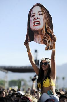 Girl in casual attire holds disembodied head of HAIM bassist Este Haim as she perches atop the shoul