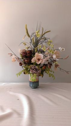 In looking at this array of stems and flowers, I was inspired to make an arrangement to accent them. The featured piece is the floral branch which pops out at you. I loved the color palette using the creamed of the magnolias to beautify the piece. The wood stems are very different. There are long stems, queen annes lace, and rananculus in a soft grey brown to make it look lovely