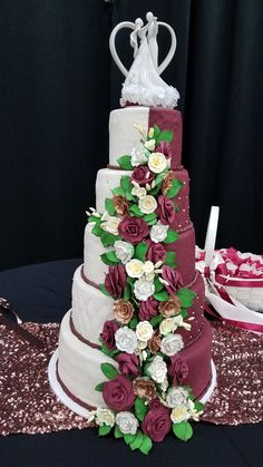 This five tier burgundy / ivory fondant cake with white, gold and burgundy roses was truly the centerpiece at the wedding