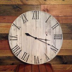 This is a large pallet clock measuring 27 1/2 in diameter. It has been made from reclaimed pallet boards. The roman numerals have been
