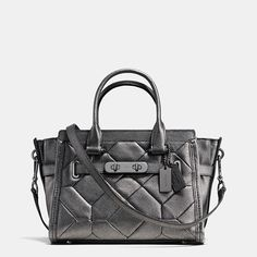 """Statement belting updates one of our most popular designs with a little bit of """"swagger."""" Thoroughly organized inside and trimmed with a bold new version of our most iconic piece of hardware, this very modern carryall is finished by hand in metallic leather with rich texture and a soft shimmer."""