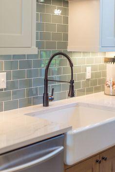 A sea green backsplash accentuates the farmhouse sink and Ella™ marble quartz countertop in this gorgeous kitchen revamp by @JKathDesignBuil