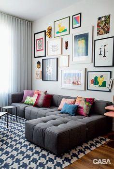 """""""COLEÇÃO DE ARTE. Molduras simples e retas unifcam o conjunto de quadros, concentrado nesta superfície. No sofá, almofadas de Fernando Jaeger e da Codex Home."""" Projeto: Mariana e André Weigand"""